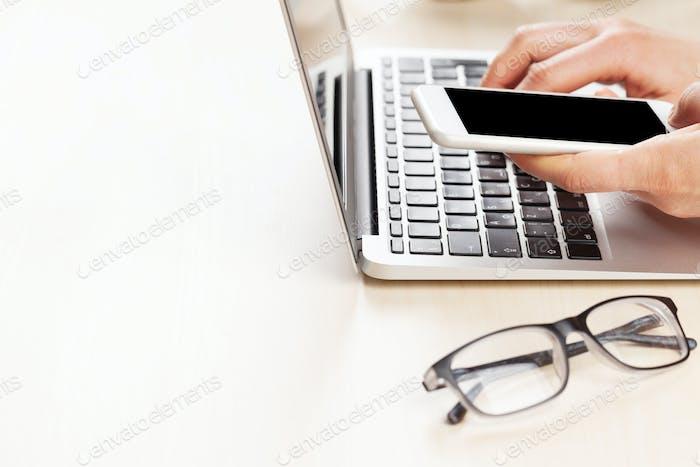 Mujer que Trabajo en la Ordenador portátil y sosteniendo el teléfono inteligente