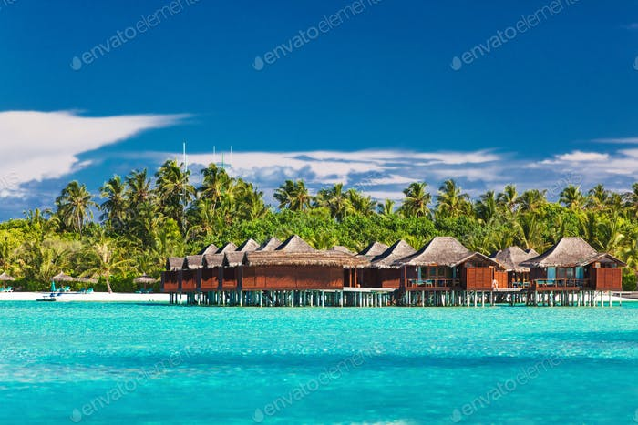 Overwater bungallows in lagoon on tropical island with coconut p