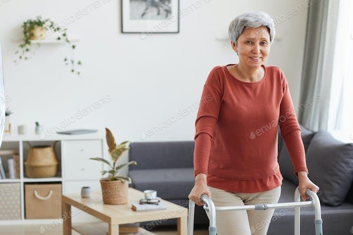 Mujer mayor usando walker en casa