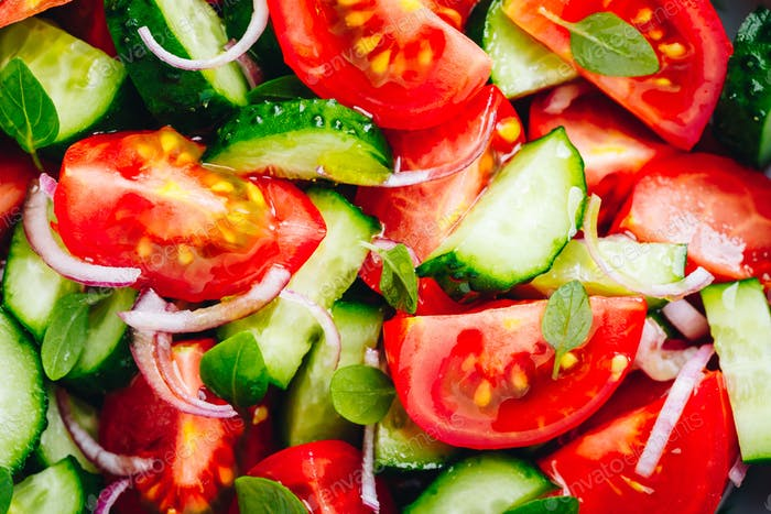 Fresh summer salad bowl with tomatoes, cucumbers, red onions, basil closeup.