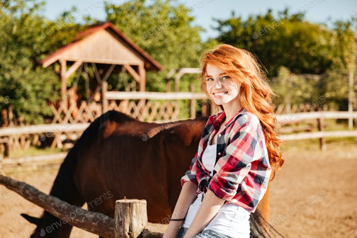 Cheerful attractive young woman cowgirl with horse in village