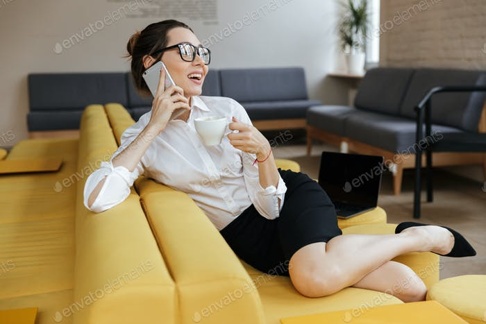 Young cheerful business woman talking by mobile phone
