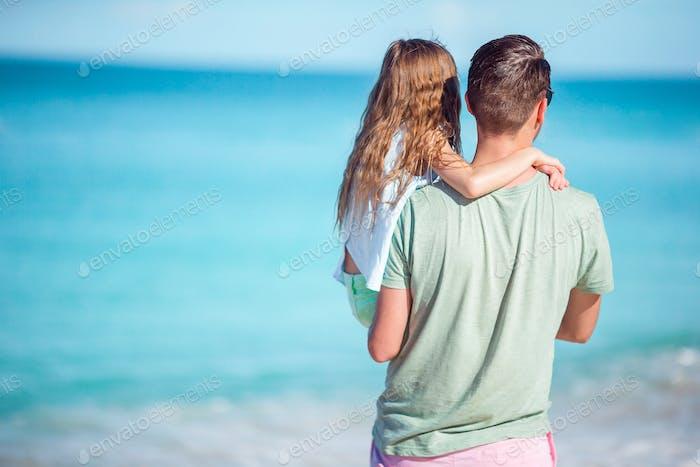 Familie am tropischen Strand zu Fuß zusammen am tropischen Carlisle Bay Strand mit weißem Sand und