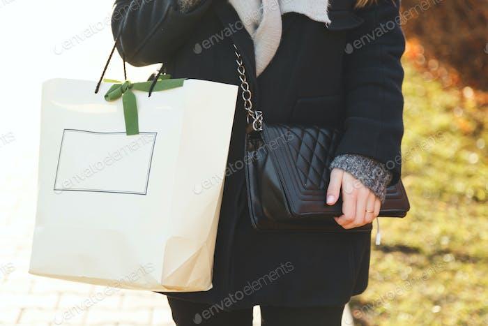 Eine Frau in einem schwarzen Mantel mit Tasche und Einkaufspack.