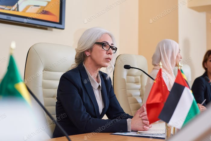 Serious mature female delegate in elegant suit listening to audience