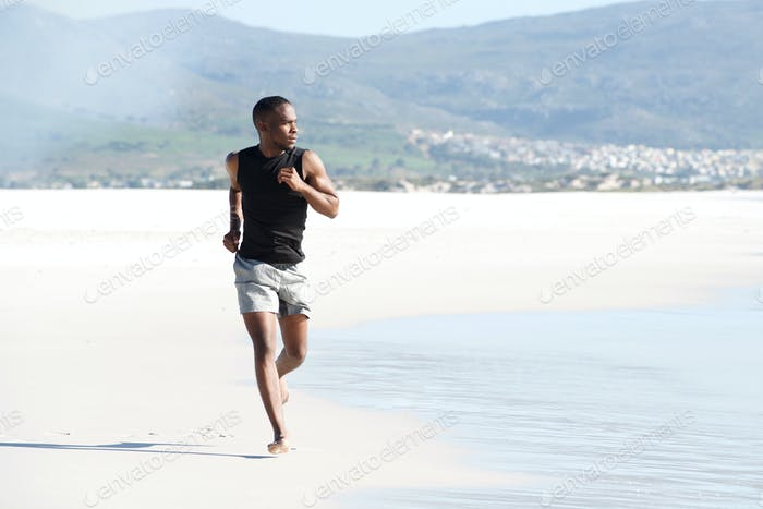 Healthy young man running on the beach in summer