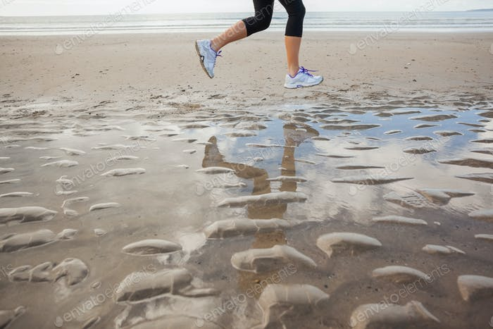 Low section of a healthy young woman jogging on shore at beach