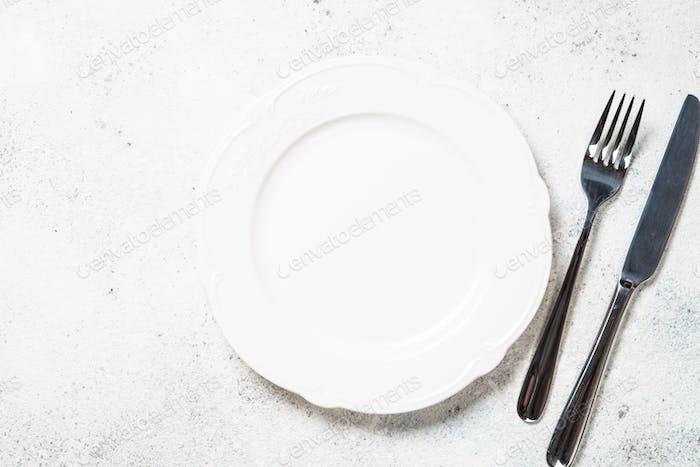 Белая тарелка и столовые приборы на белом фоне