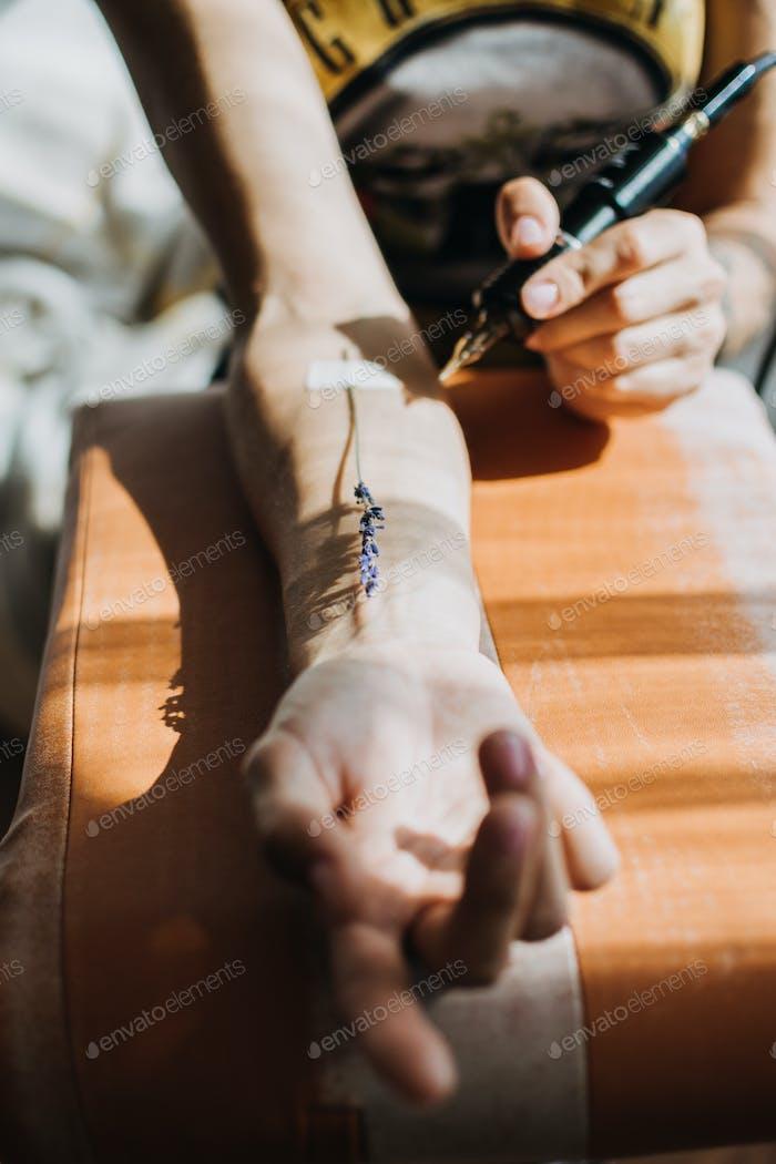 Дизайн татуировки, творческий процесс работы художника. Крупным планом рука тату мастера с татуировкой