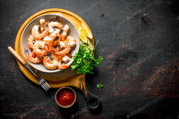 Delicious shrimps in a bowl on a cutting Board with parsley and sauce.
