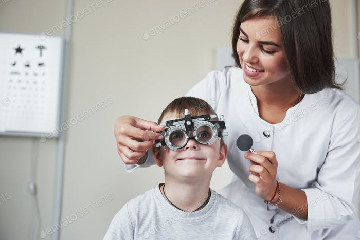 Eyes wide open. Doctor tuning the phoropter to to determine visual acuity of the little boy