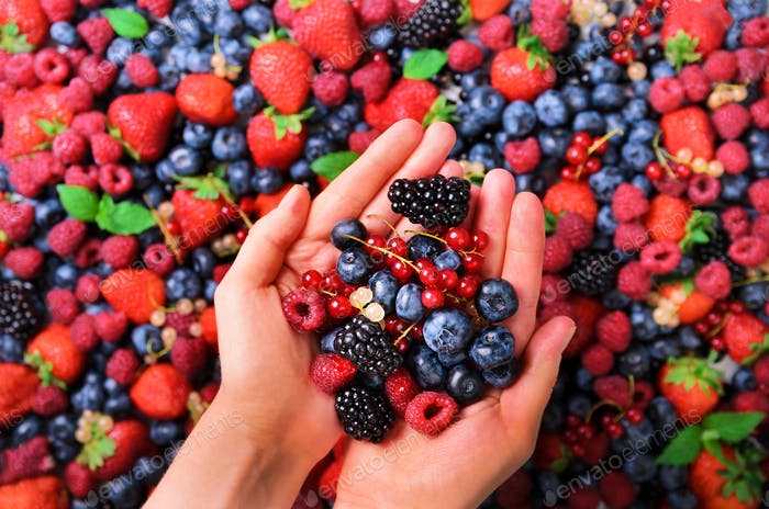 Woman hands holding organic fresh berries against the background of strawberry, blueberry