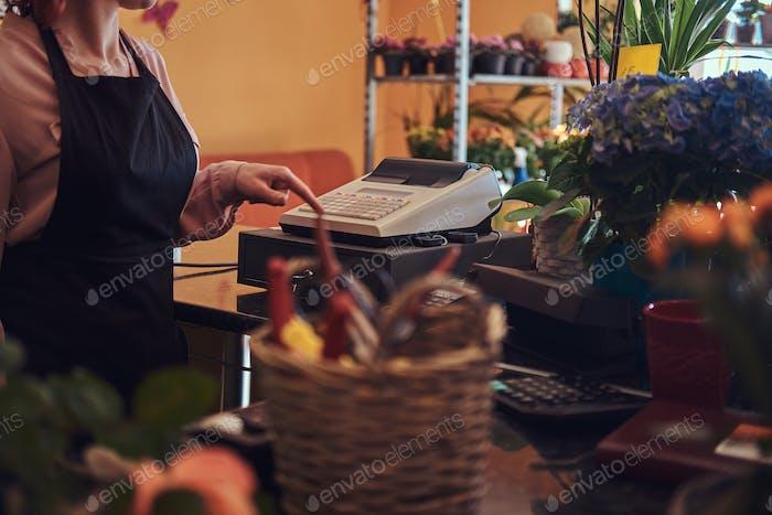 Charmante Rothaarige weibliche Floristin trägt Uniform funktioniert mit Kasse im Blumenladen.