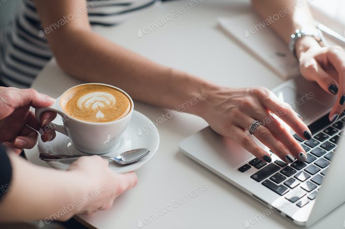 Close up picture of hands of a waiter giving a cup of cuppuccino to a woman typing with a keyboard.