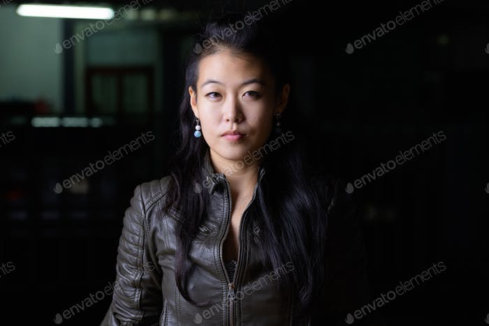 Face of beautiful Asian rebellious woman outdoors at night