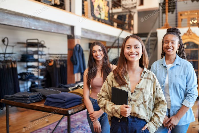 Portrait Of Smiling Multi-Cultural Female Sales Team In Fashion Store In Front Of Clothing Display