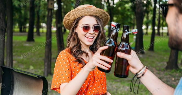 Teilansicht des Paares Clinking Flaschen Bier während des BBQ im Park