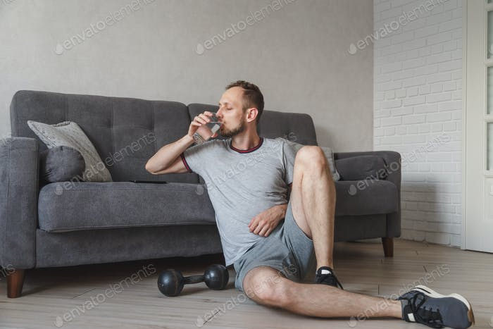Young tired man drinking water while training on in the living room. Shot at home