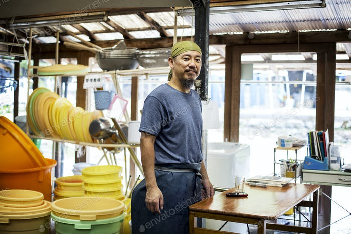 Japanese man wearing bandana standing in a textile plant dye workshop, smiling at camera.