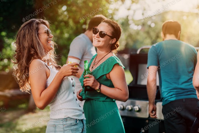 Millennials girls laughing and smiling at barbecue party, having drinks and talking with friends