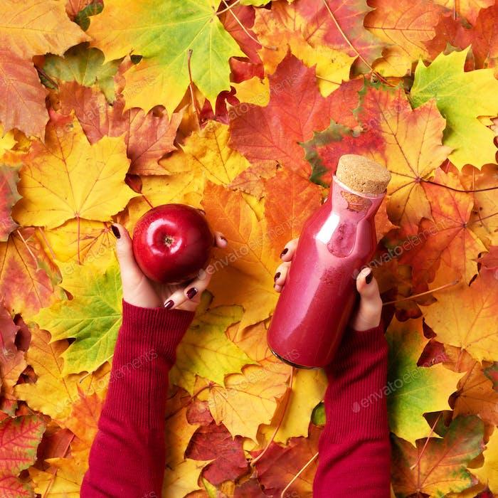 Weibliche Hände halten Flasche rotes Getränk - Smoothie oder Saft aus Gemüse, Obst und Beeren