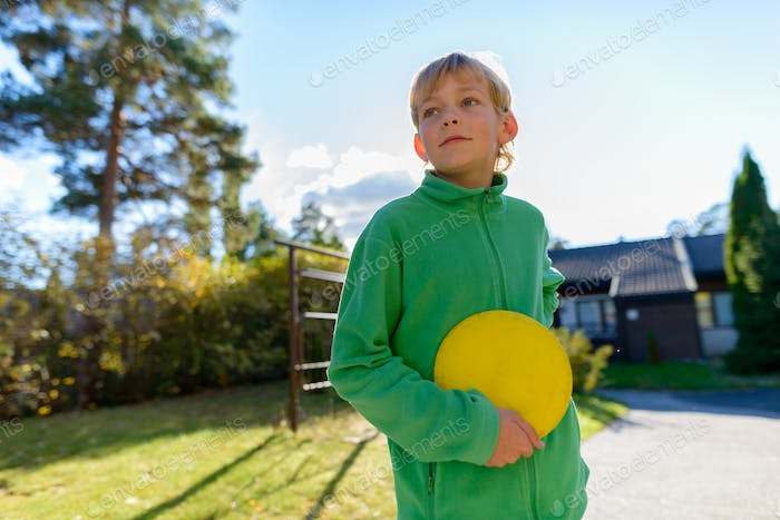 Young handsome boy playing Frisbee in the front yard
