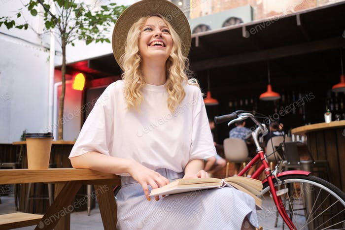 Pretty cheerful blond girl in hat joyfully sitting with book and bicycle in courtyard of city cafe