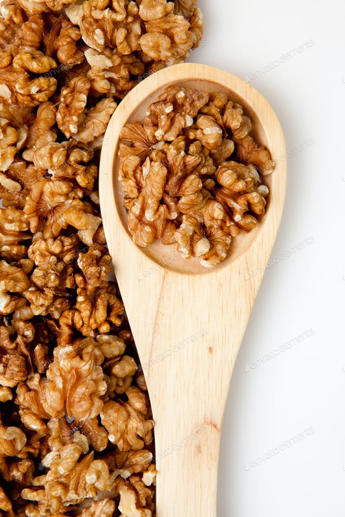Wooden spoon with nuts against a white background