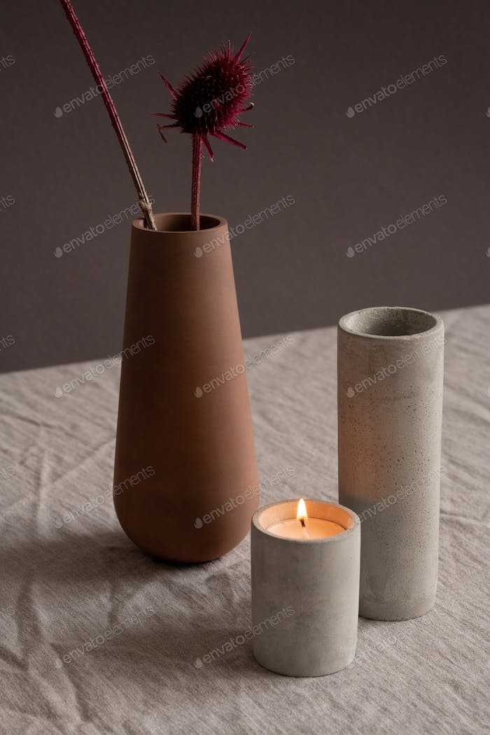 Burning candle, white ceramic vase and brown clay jug with two dry wildflowers
