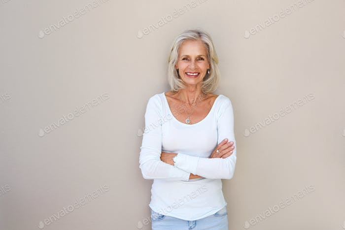 beautiful older woman standing and smiling with arms crossed