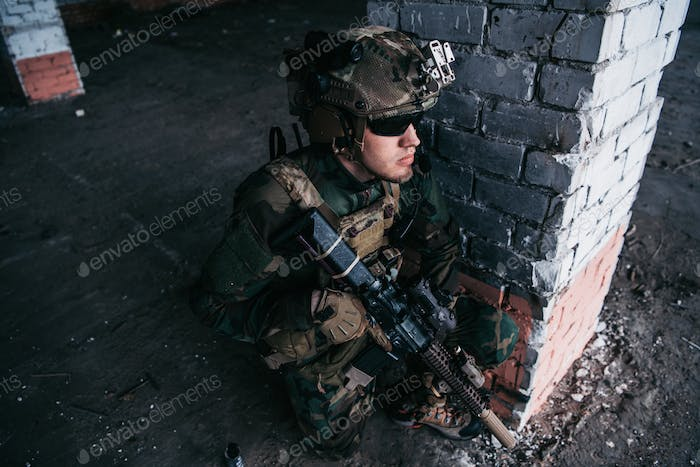 Military soldier in the form holds in the hands an assault rifle, check possible enemies around the