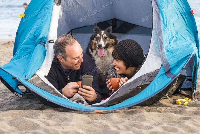 couple with dog in a tent using phone