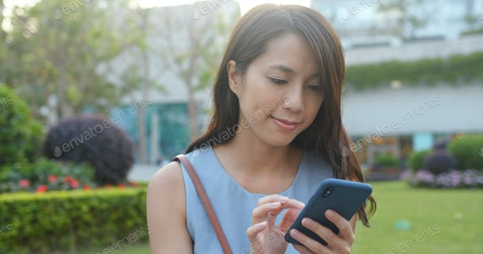 Woman use of mobile phone in the park