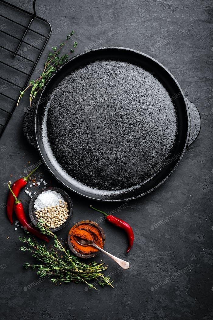 Leere Gusseisenpfanne mit Zutaten zum Kochen auf schwarzem Hintergrund, Draufsicht