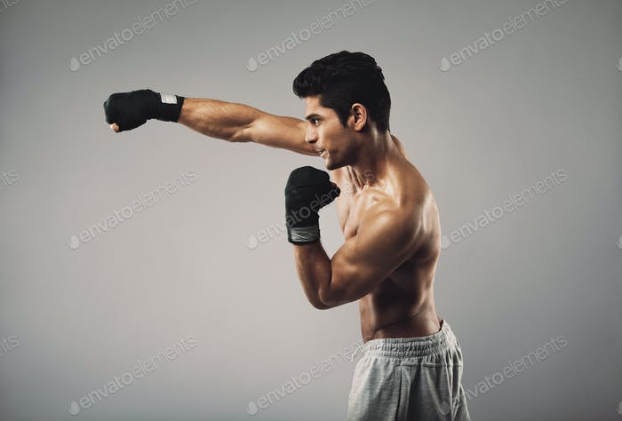 Young man practicing shadowboxing on grey background