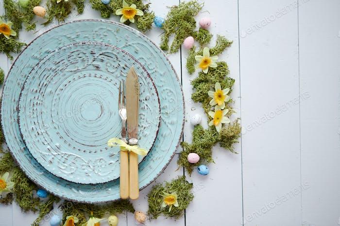 Ostertisch-Einstellung mit Blumen und Eiern. Leere dekorative Keramikteller