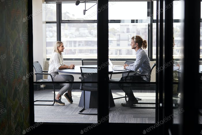 Two millennial business creatives in a meeting room for a job interview, seen through glass wall