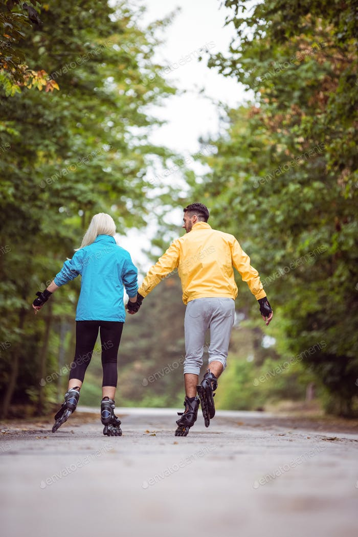 Happy couple roller blading together in the countryside