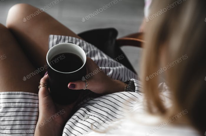 Female hands holding a white cup of tea, burgundy manicure, the girl is dressed in a shirt