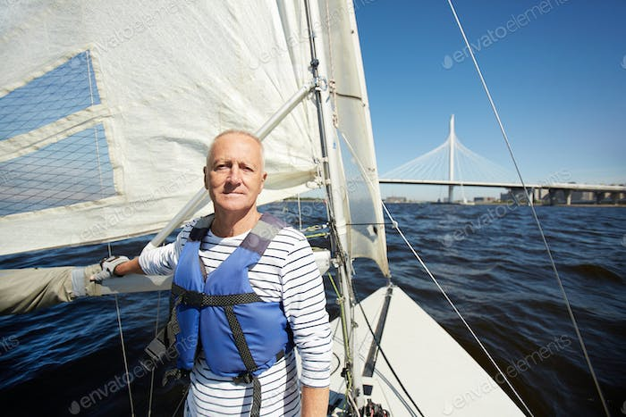 Handsome mature yacht owner in sea