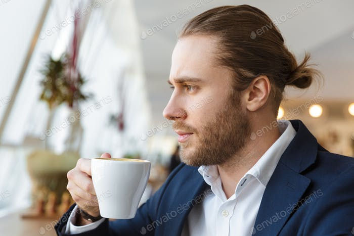 Concentrated handsome businessman drinking coffee.