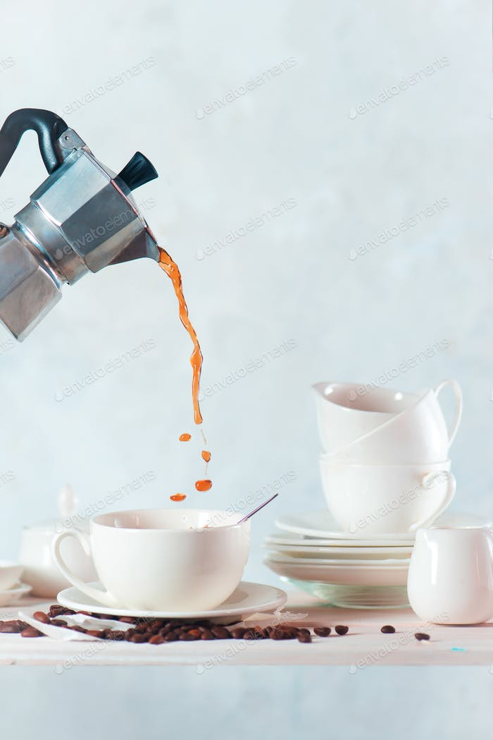 Kaffee aus einer Mokkakanne in eine Porzellantasse gießen. Weiß auf weiß stillleben mit einem Küchenregal
