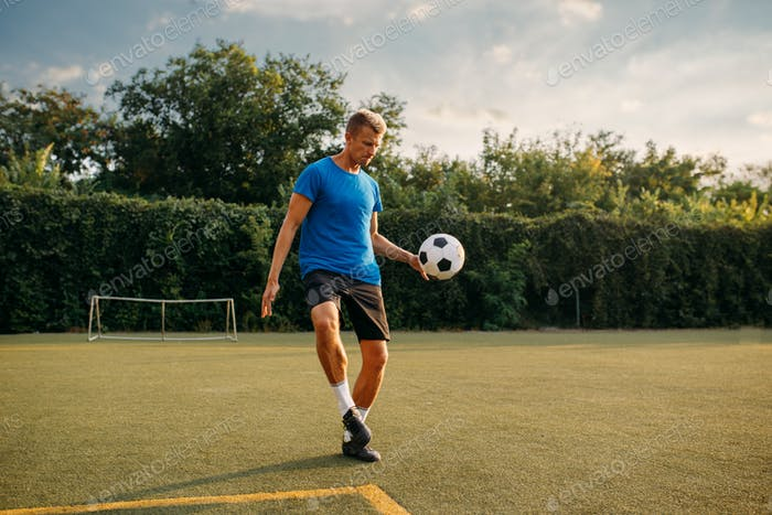 Male soccer player stuffs the ball with his foot