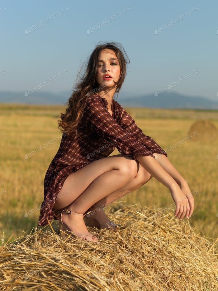 happy woman sitting on a hay stack