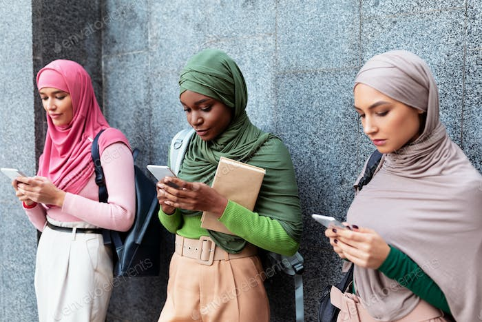 Diverse Islamic Ladies Using Phones Standing Over Gray Wall Outdoor