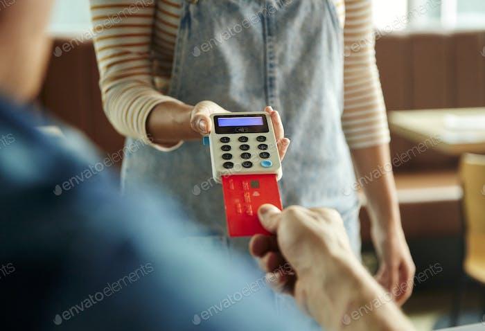 Frau hält kontaktloses Zahlungsterminal für einen mit Karte bezahlten Kunden