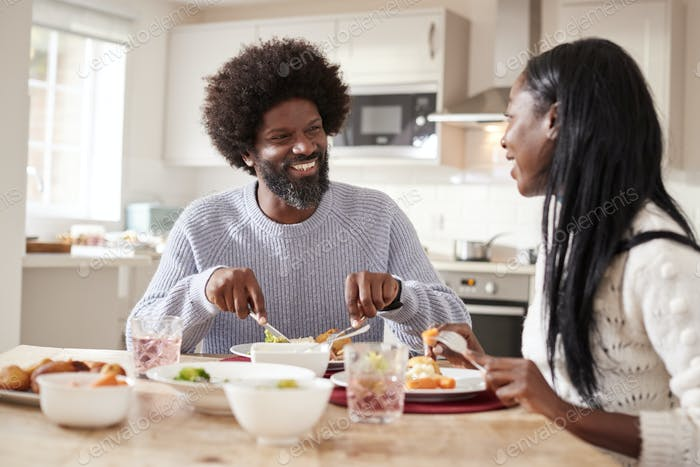 Happy black couple enjoying eating their Sunday dinner together at home, close up
