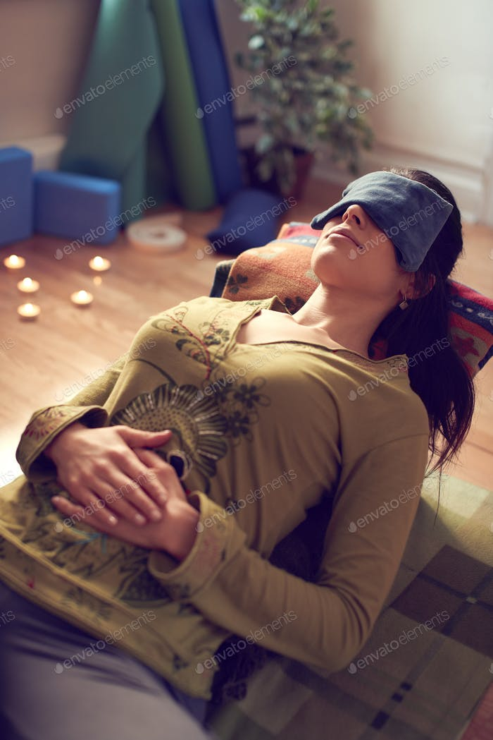 Attractive mixed race woman doing restorative yoga