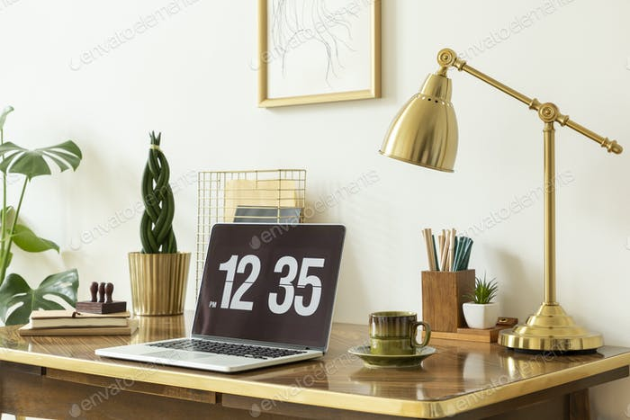 Gold lamp, laptop and plant on wooden desk in white freelancer's