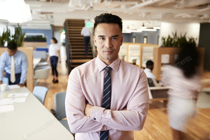 Portrait Of Businessman In Busy Modern Office With Blurred Colleagues Working In Background